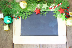 Διακόσμηση και πίνακας κιμωλίας διακοπών Χριστουγέννων στο ξύλινο υπόβαθρο Στοκ εικόνα με δικαίωμα ελεύθερης χρήσης