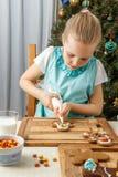 Διακόσμηση μικρών κοριτσιών του μπισκότου μελοψωμάτων Χριστουγέννων Στοκ Εικόνες