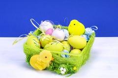 Διακόσμηση Πάσχας, γλυκό κίτρινο κοτόπουλο Πάσχας, κοτόπουλο στο πράσινα καλάθι και τα αυγά Πάσχας, στον άσπρο πίνακα και το μπλε στοκ φωτογραφία