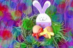 Διακόσμηση Πάσχας: κίτρινα αυγά και χέρι - το γίνοντα εορταστικό λαγουδάκι πλαστικού αφρού στους πράσινους κλαδίσκους χλόης τοποθ Στοκ φωτογραφία με δικαίωμα ελεύθερης χρήσης