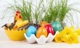 Διακόσμηση Πάσχας με τα ζωηρόχρωμα αυγά Πάσχας με τα daffodils Στοκ Φωτογραφία