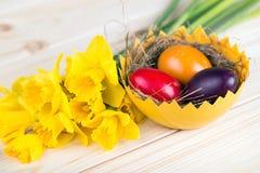 Διακόσμηση Πάσχας με τα ζωηρόχρωμα αυγά Πάσχας με τα daffodils Στοκ φωτογραφία με δικαίωμα ελεύθερης χρήσης