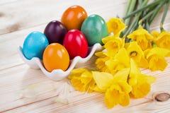 Διακόσμηση Πάσχας με τα ζωηρόχρωμα αυγά Πάσχας με τα daffodils Στοκ Εικόνες
