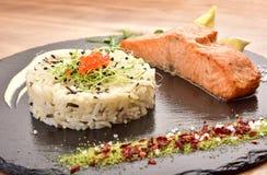 Διακόσμηση σε έναν μαύρο ξύλινο δίσκο και ένα άσπρο ρύζι και ένα κομμάτι των κόκκινων ψαριών στοκ εικόνες