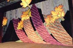 Διακόσμηση στη σκηνή που αποτελείται από Burgundy τα υφάσματα που διακοσμούνται με τα κίτρινα φύλλα στοκ εικόνες
