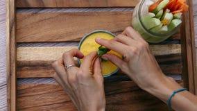 Διακόσμηση της πορτοκαλιάς φυτικής σάλτσας με την πρασινάδα στο κύπελλο r Vegan και vegeterian τρόφιμα Τρόπος ζωής της υγείας και απόθεμα βίντεο