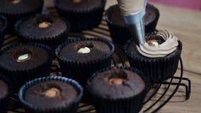 Διακόσμηση της σοκολάτας cupcake με την κρέμα Χρησιμοποίηση της μαγειρεύοντας τσάντας, ζαχαροπλάστης που κάνει cupcakes για το κό απόθεμα βίντεο