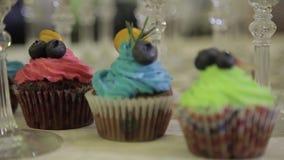 Διακόσμηση του φλυτζάνι-κέικ με την κρέμα Χρησιμοποίηση της μαγειρεύοντας τσάντας, ζαχαροπλάστης που κάνει τα πολύχρωμα cupcakes  απόθεμα βίντεο