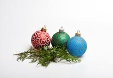 Διακόσμηση τριών σφαιρών Χριστουγέννων κοντά στον πράσινο κλάδο κυπαρισσιών Έννοια χειμερινών διακοπών Διακοσμήστε το χριστουγενν στοκ εικόνες