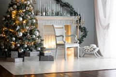 Διακόσμηση Χριστουγέννων - δωμάτιο με την όμορφα καρέκλα, την εστία και το χριστουγεννιάτικο δέντρο στοκ εικόνες με δικαίωμα ελεύθερης χρήσης