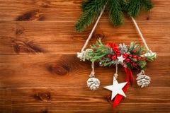 Διακόσμηση Χριστουγέννων - η σύνθεση κρεμαστών κοσμημάτων έκανε από τους κωνοφόρους κλάδους στο ξύλινο υπόβαθρο Στοκ Εικόνες