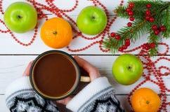 Διακόσμηση Χριστουγέννων και μια κούπα με ένα ζεστό ποτό διαθέσιμο Στοκ Εικόνες
