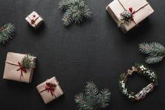 Διακόσμηση Χριστουγέννων, κιβώτια δώρων και κλαδίσκοι έλατου, τοπ άποψη με το διάστημα αντιγράφων στη μαύρη επιτραπέζια επιφάνεια Στοκ Φωτογραφίες