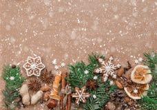 Διακόσμηση Χριστουγέννων με τα καρυκεύματα και τα μπισκότα με μορφή snowflakes στο σκοτεινό υπόβαθρο καφετιού εγγράφου Τοπ όψη στοκ φωτογραφίες