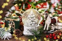 Διακόσμηση Χριστουγέννων με τη σφαίρα χιονιού γυαλιού, το άλογο λικνίσματος και το φανάρι στοκ εικόνα