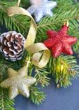 Διακόσμηση Χριστουγέννων με τον κλάδο δέντρων έλατου, τα λάμποντας αστέρια Χριστουγέννων, τη χρυσούς κορδέλλα και τον κώνο πεύκων Στοκ Φωτογραφία
