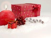 Διακόσμηση Χριστουγέννων με το κόκκινο κερί κόκκινα δώρα στο χιόνι Στοκ Φωτογραφίες