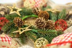 Διακόσμηση Χριστουγέννων με: Το στεφάνι Χριστουγέννων, κλάδοι πεύκων, κώνοι πεύκων, κίτρινοι ακτινοβολεί αστέρια Χριστουγέννων Στοκ εικόνα με δικαίωμα ελεύθερης χρήσης