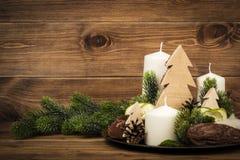 Διακόσμηση Χριστουγέννων που γίνεται από τα κεριά και τα floristic εξαρτήματα στο ξύλινο υπόβαθρο Στοκ Εικόνα