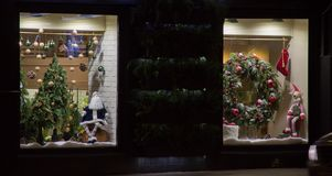 Διακόσμηση Χριστουγέννων σε μια προθήκη Κούκλα Άγιου Βασίλη, χριστουγεννιάτικο δέντρο, κάλτσα, στεφάνι διακοπών, τάρανδος Santa ` Στοκ Φωτογραφίες
