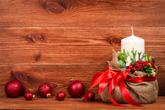 Διακόσμηση Χριστουγέννων - σύνθεση Χριστουγέννων με την τσάντα, το άσπρες κερί και τις σφαίρες στο ξύλινο υπόβαθρο Στοκ Φωτογραφία