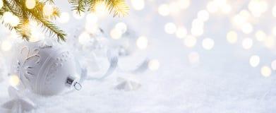 Διακόσμηση Χριστουγέννων τέχνης και φως διακοπών στο υπόβαθρο χιονιού Στοκ Εικόνα
