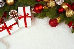 Διακόσμηση Χριστουγέννων ως υπόβαθρο, δώρα, σφαίρα Χριστουγέννων, κώνος και άλλο αντικείμενο στην άσπρη κενή διαστημική γούνα, έν στοκ εικόνες