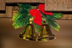 Διακόσμηση Χριστουγέννων, δύο λαμπρά χρυσά κουδούνια με τον κλάδο έλατου Στοκ Φωτογραφίες