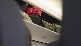 Διαμέρισμα αποσκευών στο αεροπλάνο με τη χειραποσκευή απόθεμα βίντεο