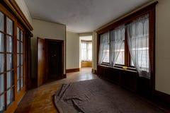 Διαμέρισμα με τα μεγάλα παράθυρα και τα πατώματα σκληρού ξύλου - εγκαταλειμμένο Rectory εκκλησιών στοκ φωτογραφίες με δικαίωμα ελεύθερης χρήσης