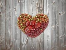 Διαμορφωμένα καρδιά φρούτα με το ξύλινο υπόβαθρο Στοκ Εικόνα