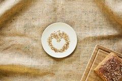 Διαμορφωμένα καρδιά crumbs ψωμιού στο πιάτο με το ψωμί Στοκ Εικόνα