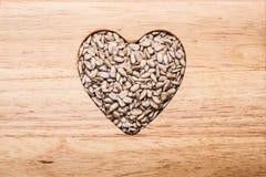 Διαμορφωμένοι καρδιά σπόροι ηλίανθων στην ξύλινη επιφάνεια στοκ εικόνα