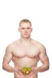 Διαμορφωμένος και υγιής άνδρας σωμάτων που κρατά μια φρέσκια σαλάτα Στοκ Εικόνες