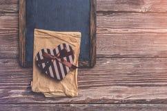 Διαμορφωμένο καρδιά κιβώτιο δώρων ημέρας βαλεντίνων σε έναν πίνακα κιμωλίας Στοκ Φωτογραφία