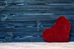 Διαμορφωμένο καρδιά μαξιλάρι στον ξύλινο τοίχο Στοκ Εικόνες