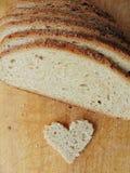 Διαμορφωμένο καρδιά κομμάτι του ψωμιού μπροστά από το πλήρες ψωμί Στοκ Φωτογραφία