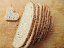 Διαμορφωμένο καρδιά κομμάτι του ψωμιού μπροστά από το πλήρες ψωμί Στοκ εικόνες με δικαίωμα ελεύθερης χρήσης