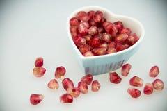 Διαμορφωμένο καρδιά πιάτο, κόκκινα φρούτα ροδιών Στοκ Φωτογραφία