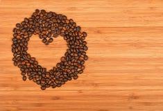 Διαμορφωμένο καρδιά πλαίσιο φασολιών καφέ πέρα από το ξύλινο υπόβαθρο μπαμπού Στοκ Φωτογραφία