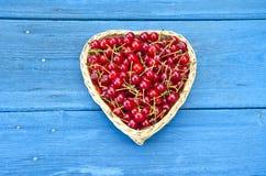 Διαμορφωμένο καρδιά ψάθινο σύνολο καλαθιών των κερασιών στο μπλε υπόβαθρο Στοκ Εικόνα