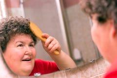 Διανοητικά - με ειδικές ανάγκες γυναίκα που κτενίζει μέσω της τρίχας της στοκ εικόνες