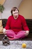 Παρεμποδισμένη συνεδρίαση γυναικών cross-legged στον καναπέ Στοκ φωτογραφία με δικαίωμα ελεύθερης χρήσης