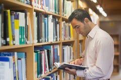 Διανοητικό άτομο που διαβάζει ένα βιβλίο που στέκεται στη βιβλιοθήκη Στοκ φωτογραφία με δικαίωμα ελεύθερης χρήσης