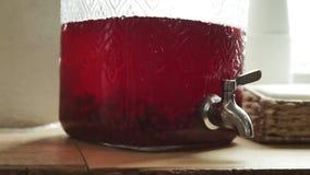 Διανομέας κύπελλων λεμονάδας με τη βρύση με compote για ένα κόκκινο λεμονάδας μούρων κομμάτων απόθεμα βίντεο