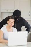 Διαρρήκτης που εξετάζει το lap-top πίσω από τη γυναίκα Στοκ Εικόνα
