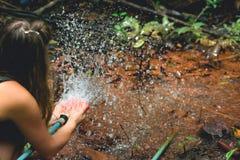 Διασκέδαση ανύψωσης γυναικών με hosepipe το καταβρέχοντας νερό στοκ φωτογραφία με δικαίωμα ελεύθερης χρήσης