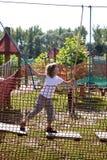 Διασκέδαση στο σχοινί πάρκων - το κορίτσι υπερνικά τα εμπόδια Στοκ εικόνα με δικαίωμα ελεύθερης χρήσης