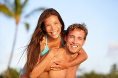 Διασκέδαση ζευγών διακοπών στην παραλία, άτομο που δίνει piggyback Στοκ εικόνα με δικαίωμα ελεύθερης χρήσης