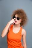 Διασκέδαση του αρκετά σγουρού θηλυκού που θέτει και γυαλιά ηλίου καθορισμού Στοκ φωτογραφία με δικαίωμα ελεύθερης χρήσης
